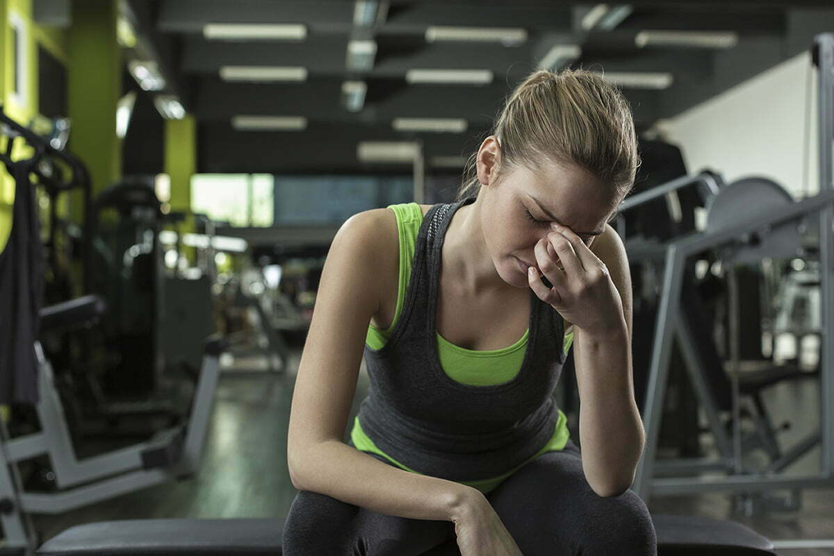 Woman with a headache sitting at the gym