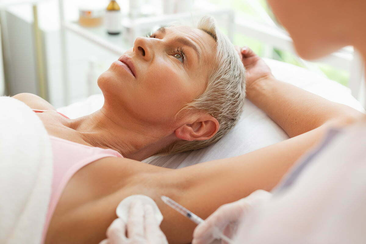 reclined woman presents armpit for botox injection from doctor
