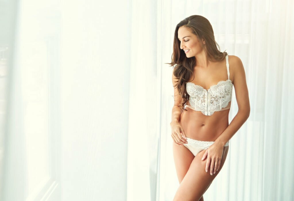 Beautiful Woman in Bedroom Considers Tummy Tuck or Liposuction with Hess Plastic Surgery
